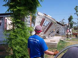 A volunteer in a blue shirt at a site affected by severe storm damage.